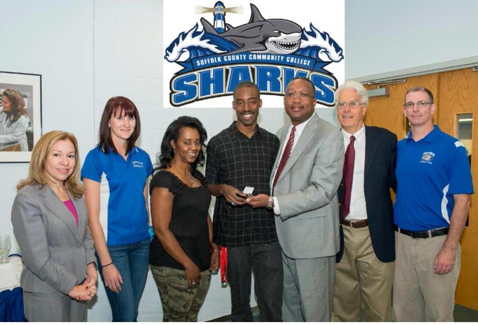 Suffolk County Community College student-athlete, Dannie Holland (center), received an NJCAA 2013 National Championship ring for in recognition of his National Title in the Triple Jump. Seen at the presentation ceremony are (left to right): Dafny J. Irizarry, Chairwoman of the College's Board of Trustees; Lauren Biscardi, Assistant Track and Field Coach; Dannie's mother Deon Holland; Dannie Holland; Dr. Shaun L. McKay, President of Suffolk County Community College; Kevin Foley, Interim College Director of Athletics, and Matthew French, the College's Head Track and Field Coach.